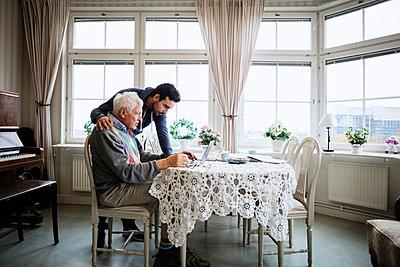 Senior man using laptop with caretaker at nursing home - p426m1131143f by Maskot