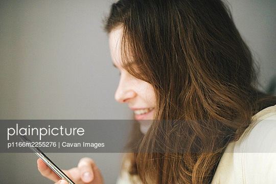 Woman  using smartphone at  home - p1166m2255276 by Cavan Images