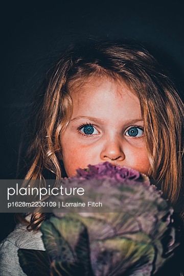 Blue-eyed girl holds ornamental cabbage - p1628m2230109 by Lorraine Fitch