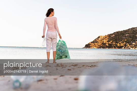 Back view of woman standing on the beach with bin bag of collected empty plastic bottles - p300m2143719 by Daniel Ingold