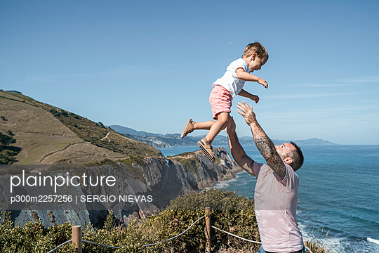 Father catching son at observation point against blue sky on sunny day - p300m2257256 by SERGIO NIEVAS