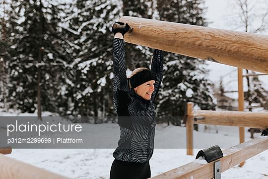 Smiling woman exercising at winter - p312m2299699 by Plattform