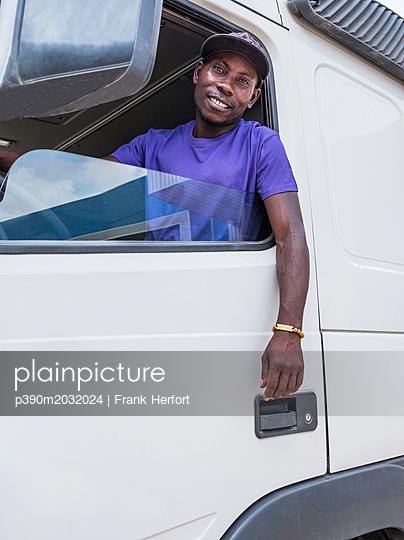 Afrikanischer Lkw Fahrer schaut aus seiner Fahrerkabine - p390m2032024 von Frank Herfort