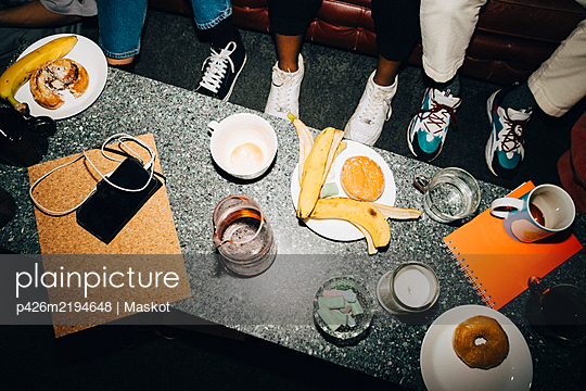 High angle view of food and drink on table in creative office - p426m2194648 by Maskot