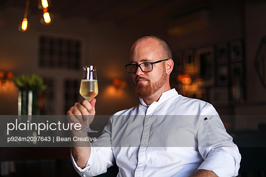Portrait of chef with glass of wine in luxury restaurant - p924m2097643 by Bean Creative