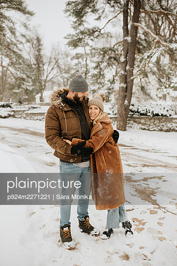 Canada, Ontario, Hugging couple standing on snowy road - p924m2271221 by Sara Monika
