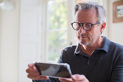 Focused mature man using smart phone - p1023m1577432 by Sam Edwards