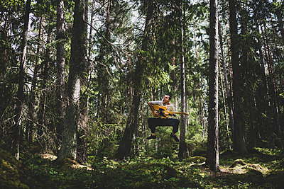 Man playing guitar in the forest - p1295m2133333 by Katharina Bauer