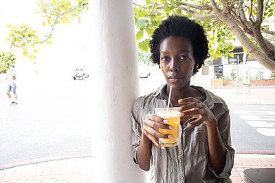 Young African woman has a soft drink - p1640m2260096 by Holly & John