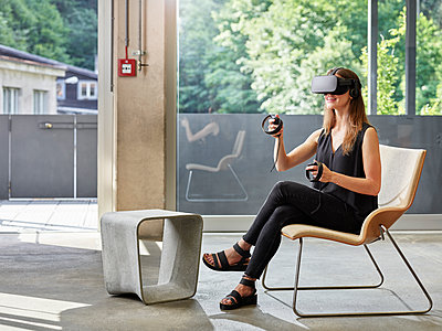 Smiling woman wearing VR glasses sitting on chair - p300m1549540 by Christian Vorhofer