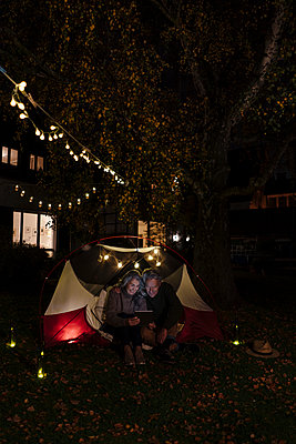 Senior couple with tablet camping in garden of their home at night - p300m2156250 by Gustafsson