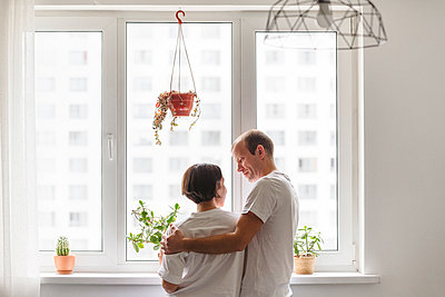 Man and woman looking at each other while embracing near window at home - p300m2277714 by Katharina und Ekaterina