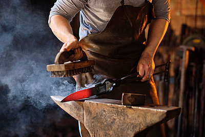 Young male craftsperson preparing metal knife on anvil at workshop - p300m2281447 by Antonio Ovejero Diaz