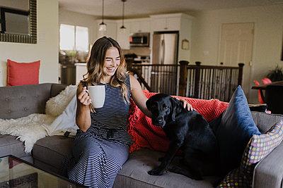 Woman enjoying cup of hot beverage, stroking dog on sofa - p429m2146022 by Sara Monika