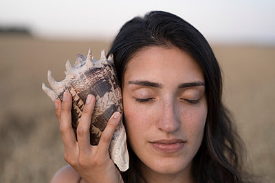 Young woman listening to shell - p552m1462153 by Leander Hopf