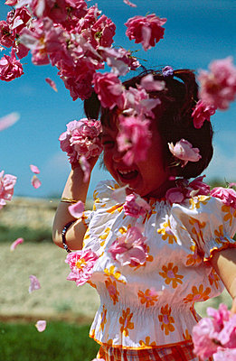 Little girl in a shower of petals - p8850018 by Oliver Brenneisen