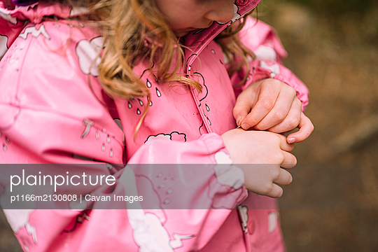 Curious girl with spruce needle in woods - p1166m2130808 by Cavan Images