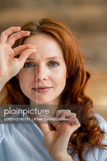 Portrait of redheaded woman holding thread of dental floss - p300m2140781 by Kniel Synnatzschke
