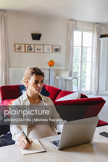 Female freelancer writing in book while using laptop at desk in living room - p300m2243184 by Michela Ravasio