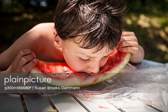 Boy eating watermelon - p300m950082f by Susan Brooks-Dammann