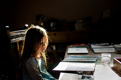 A small child reads a book at at table in early morning sunlight - p1166m2095966 by Cavan Images