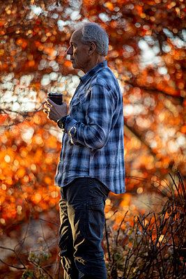Man holding coffee cup by autumn trees - p1427m2109955 by Steve Smith