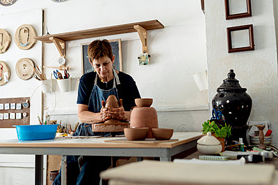 Mature female artist making pottery from brown clay in ceramic store - p300m2240349 by Ezequiel Giménez