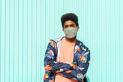 Man with arms crossed wearing protective face mask in front of turquoise wall - p300m2273513 by VITTA GALLERY