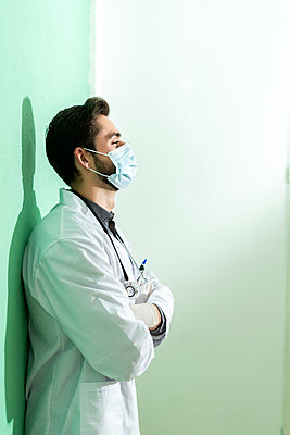 Male medical expert wearing face mask standing with arms by wall - p300m2274658 by Giorgio Fochesato