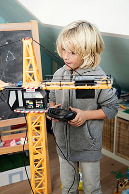 Blond boy playing with toy crane - p300m873913f by Gabi Dilly