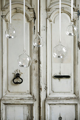 Clear glass baubles hanging on ribbons with twinkling tealights in front of an old ornate panelled front door - p3493125 by Jon Day