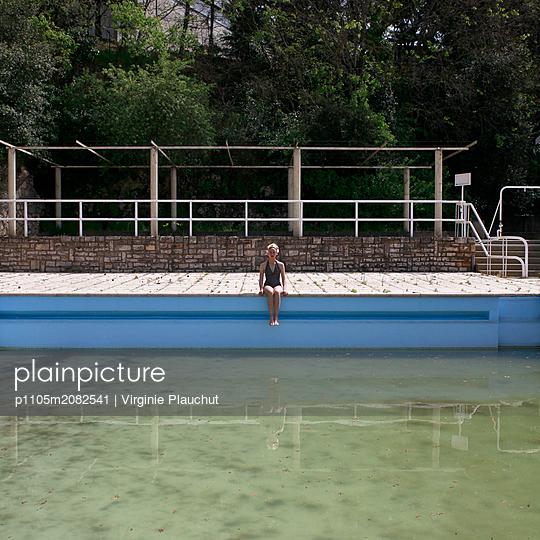 Frau sitzt am Beckenrand - p1105m2082541 von Virginie Plauchut