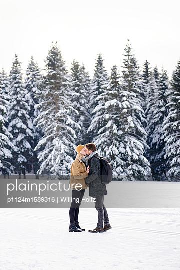 Junges Paar küsst sich in einer Schneelandschaft - p1124m1589316 von Willing-Holtz