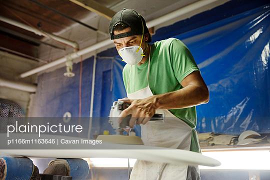 Worker using sander machine on surfboard in workshop - p1166m1163646 by Cavan Images