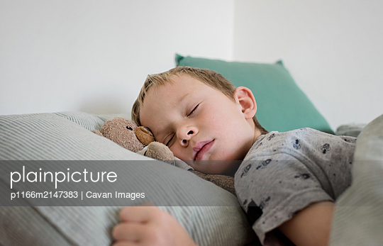 young boy sleeping with his bear in bed at home - p1166m2147383 by Cavan Images