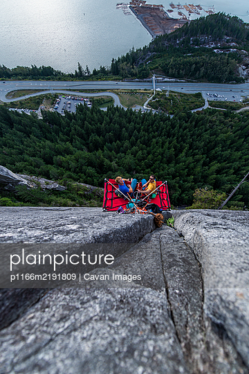 Top view of two men looking up and sitting on portaledge at sunset - p1166m2191809 by Cavan Images