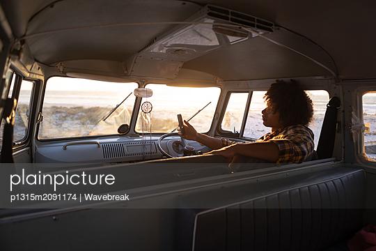 Man using mobile phone in camper van at beach - p1315m2091174 by Wavebreak