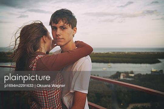Junges Paar auf einem Balkon über der Stadt - p1694m2291633 von Oksana Wagner