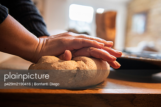 Close up of person standing in kitchen, kneading bread dough. - p429m2190416 by Bonfanti Diego