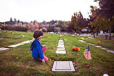 Side view of boy kneeling at cemetery - p1166m1210172 by Cavan Images