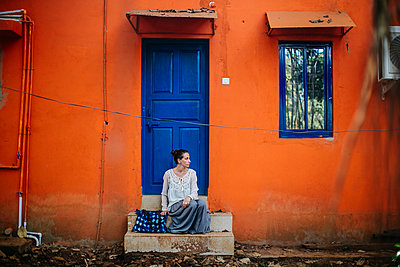 Woman sitting on steps in front of the house - p1414m1590571 by Dasha Pears