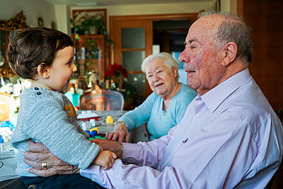 Great-grandparents playing with baby girl at home - p300m1563275 by Gemma Ferrando