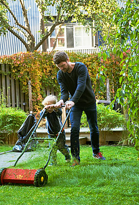 Sweden, Skane, Osterlen, Borrby, Father and son (4-5) mowing lawn in domestic garden  - p352m1061431f by Thyra Brandt