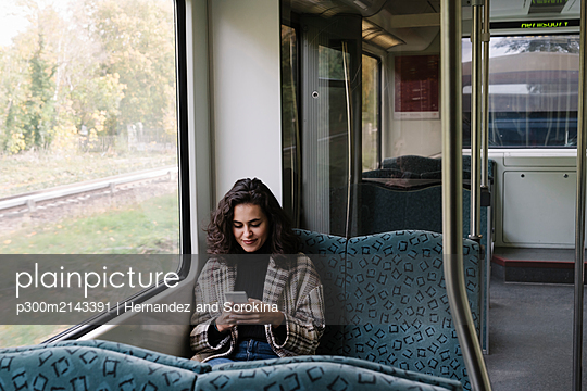 Young woman using smartphone on a subway - p300m2143391 by Hernandez and Sorokina