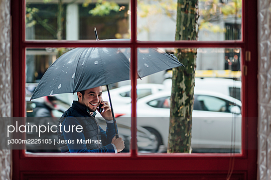 Happy man with umbrella talking on smart phone while looking at window during rainy season - p300m2225105 by Jesús Martinez