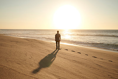 Man on beach at sunset - p1124m1510936 by Willing-Holtz