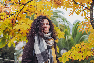 Pretty woman in a scarf with hair on her face, orange leaves, autumn - p1166m2212444 by Cavan Images