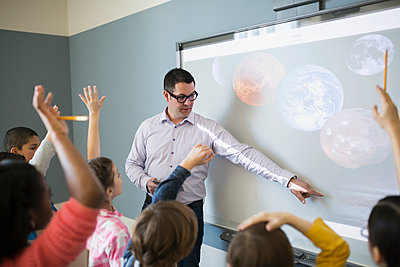 Teacher leading astronomy lesson at screen - p1192m1019864f by Hero Images