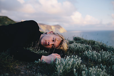 Blond boy lies on green grass on a hill near the sea - p1363m1424649 by Valery Skurydin