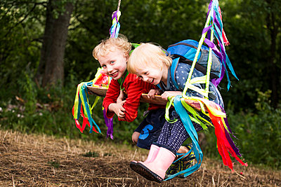Portrait of boy and his little sister having fun with a swing - p300m2160566 by Irina Heß